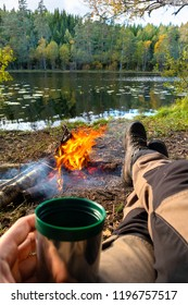 Man relaxing ourdoor by the fire in the forest with a coffee