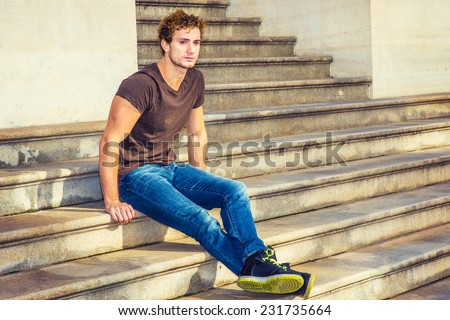 Man Relaxing Outside. Wearing dark brown T shirt, blue jeans, black sneakers, a young sexy guy with curly hair is sitting on stairs outside office, stretching legs, crossing, thinking.