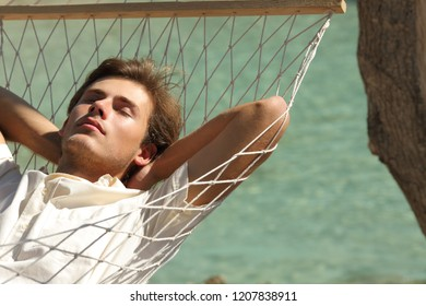 Man relaxing resting on a hammock on vacation with a turquoise sea in the background