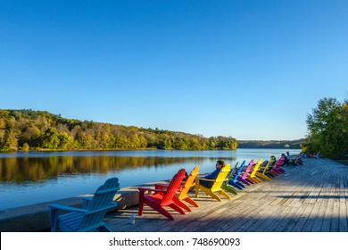 Man relaxing in a row of brightly colored adirondack chairs along waterfront in fall