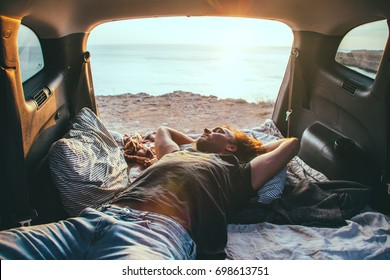 Man relaxing and sleeping inside car trunk. Fall trip in sunset. Freedom travel concept. Autumn weekend.