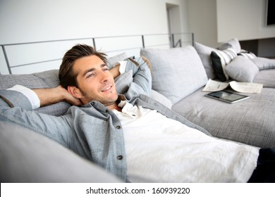Man relaxing in sofa with arms behind head