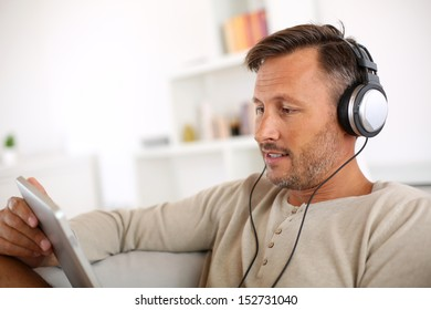 Man relaxing in sofa with tablet and headphones on