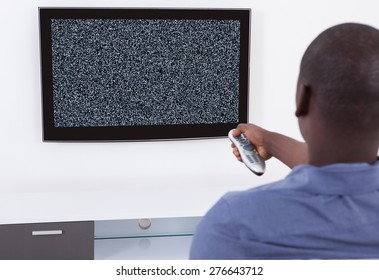 Man With Remote Control In Front Of Television With No Signal