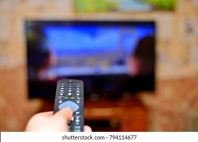 The man with the remote control in hand watching the sports channel and presses the button on the remote control. Remote control in hand closeup.