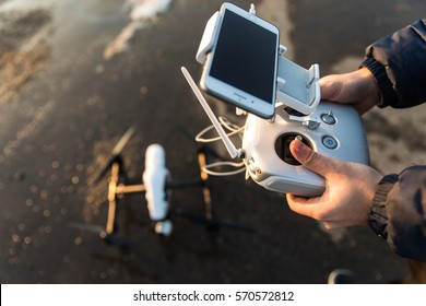 Man with remote control prepare white drone with digital camera for start flying in winter
