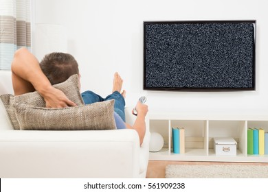 Man With Remote Control Relaxing On Couch In Front Of Television Showing No Signal At Home