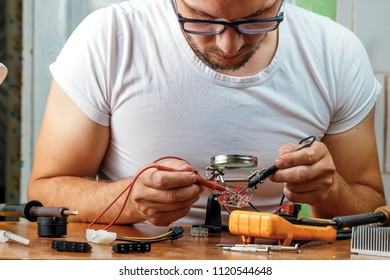 The man remotes the microcircuit. Workplace with soldering iron, microcircuit, magnifying glass, magnifying glass, measuring instruments. Electronics repair, master.