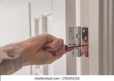 Man remove the door. Twists self-tapping screw with a screwdriver. Stainless door hinges on a white door