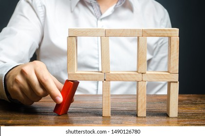 The man removes the red structural element, which will collapse. Destruction of a complex structure by negligence. Incompetent businessman. Loss of key elements and employees. Damage to the opponent.