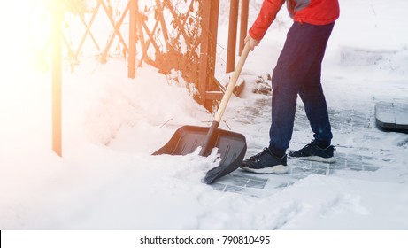 A man removes snow from the sidewalk after a blizzard. to clean snow with a shovel after a snowfall. clean the yard.