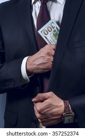 Man removes US dollars in his suit pocket on a grey background. Vertical view.