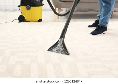 Man removing dirt from carpet with vacuum cleaner indoors, closeup