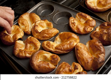 Man removing freshly baked individual fluffy golden Yorkshire puddings from a baking tray