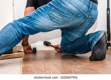 Man removing laminate on the floor in socks