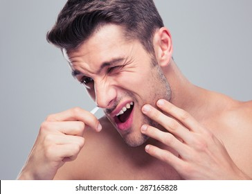 Man removing nose hair with tweezers over gray background