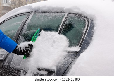 Man removing snow cover from car after snowfall
