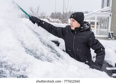 Man removing snow from his car after a snow storm.