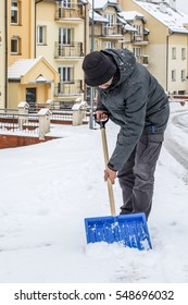 Man removing snow from the sidewalk after snowstorm