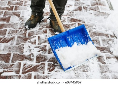 Man removing snow from the sidewalk after snowstorm.