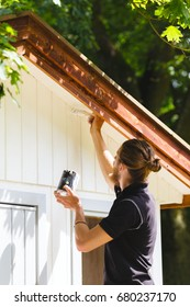 man renovate wooden house. painting walls with oil-based white color. varnishing home exterior with paintbrush.