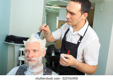 man repaint the hair in a beauty salon