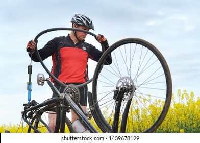 a man repairing a Bicycle in a field, a puncture of a Bicycle camera on the way, Kaliningrad region, Russia, may 19, 2019