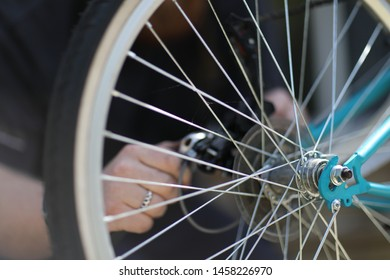 A man is repairing a bicycle with a tool in his hands.