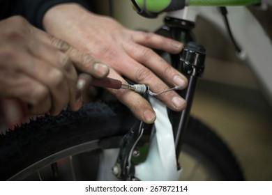 man repairing a bike with a screwdriver