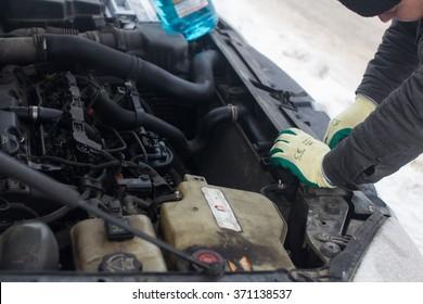 man repairing a car in winter