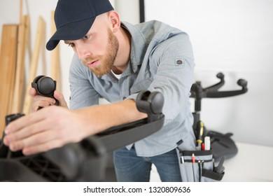 man repairing a chair by hand