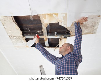 Man repairing collapsed ceiling. Ceiling panels damaged  huge hole in roof from rainwater leakage.Water damaged ceiling .