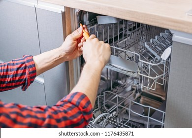 man repairing dishwasher. Male hand with screwdriver installs kitchen appliances, close up