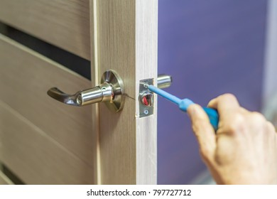 Man Repairing The Doorknob With Screwdriver. Workeru0027s Hand Installing New  Door Locker