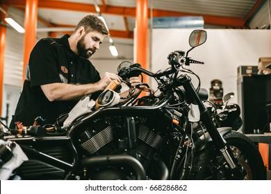Man repairing electronics sports black bike. Confident young man repairing motorcycle in repair shop.