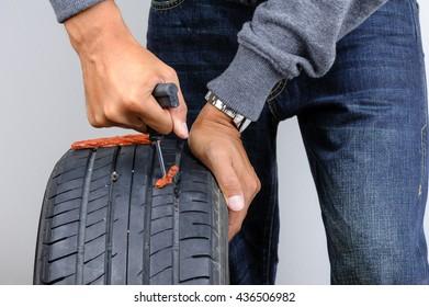 The man repairing flat car tire with repair kit, Tire plug repair kit for tubeless tires.