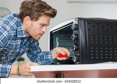 man repairing microwave