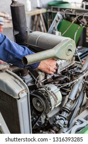 Man repairing old dirty car engine