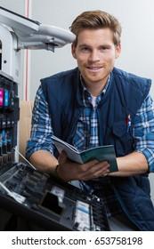 Man repairing photocopier holding manual