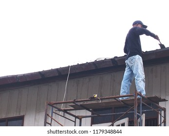 A man repairing the roof.