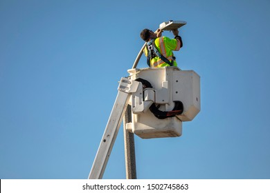Man repairing street light in bucket with blue sky background