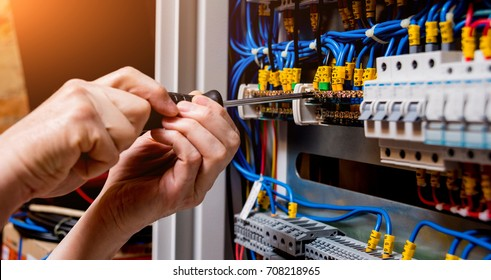 The man is repairing the switchboard voltage with automatic switches. Electrical background