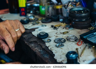 Man is repairing the watches (close look at the detais) on a Street market in Vientiane, Laos