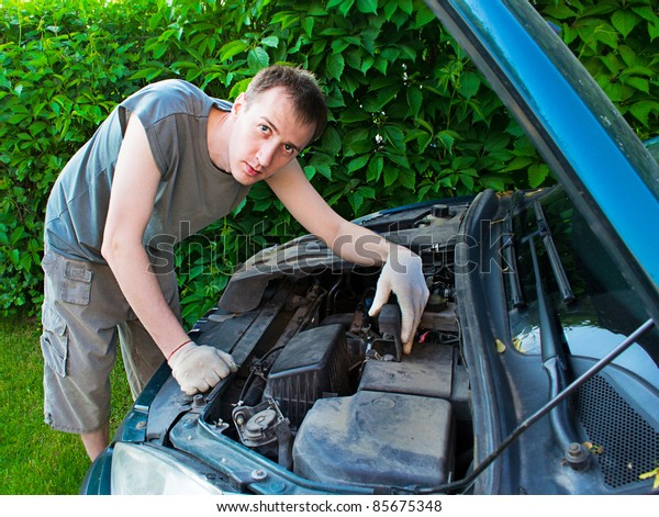 The man repairs the car