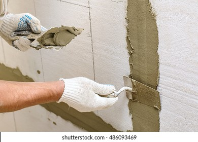 Man repairs wall with spackling paste, Construction industry worker using a putty knife and leveling concrete on concrete pillars, Worker spreading plaster to wall, corner protecting batten install