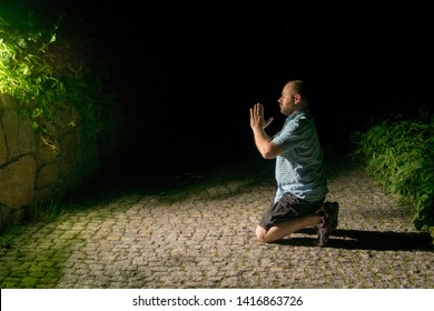 A man repents praying at night in nature.