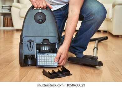 Man replacing an air  filter of a vacuum cleaner at home.