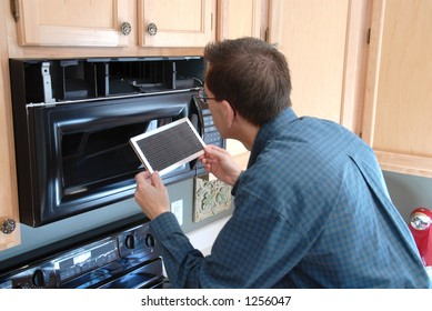 Man replacing the filter in a microwave in the kitchen of a modern home.