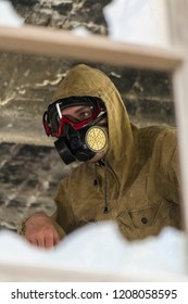 Man in respirator gas mask and and biological and chemical protection clothes with hood. view through a broken window