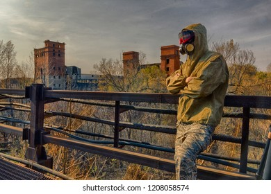 Man in respirator gas mask and special protective clothing stain on front of abandoned ruins of industrial building. Maybe radioactive zone or contaminated bad air, or biological hazard